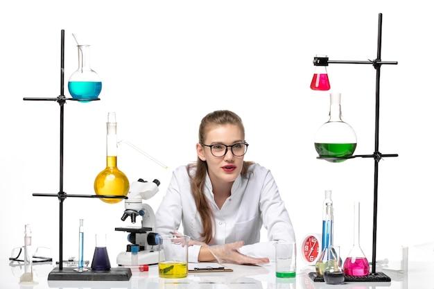Вид спереди женщина-химик в медицинском костюме, сидящая с разными растворами на белом фоне, пандемия здоровья, химия, covid