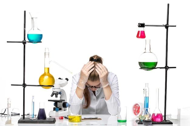Вид спереди женщина-химик в медицинском костюме сидит с растворами и чувствует усталость на белом фоне пандемического химического вируса covid-