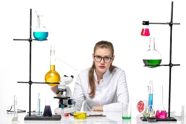 흰색 배경에 대유행 화학 covid- 바이러스에 솔루션 및 현미경으로 앉아 의료 소송에서 전면보기 여성 화학자