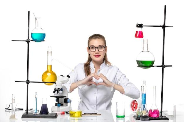Вид спереди женщина-химик в медицинском костюме, сидящая с растворами и показывающая знак любви на белом фоне, пандемический вирус химии