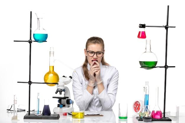 밝은 흰색 배경 유행성 화학 covid- 바이러스에 솔루션과 함께 앉아 의료 소송에서 전면보기 여성 화학자
