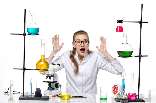 흰색 배경 화학 전염병 covid- 바이러스에 솔루션과 함께 앉아 의료 소송에서 전면보기 여성 화학자