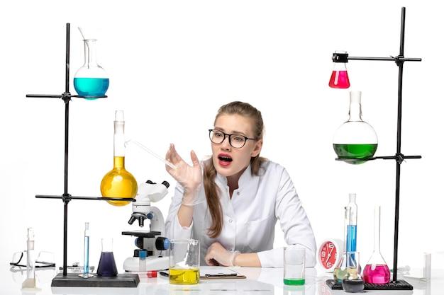 흰색 배경에 대유행 화학 covid- 바이러스에 솔루션과 함께 앉아 의료 소송에서 전면보기 여성 화학자