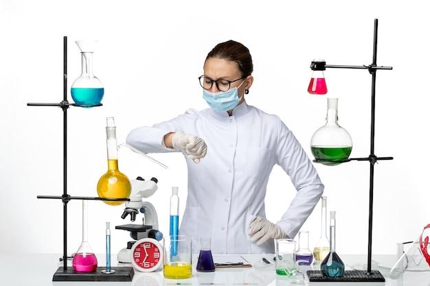 白い背景の上の彼女の手首を見ているマスクを身に着けている医療スーツの正面図女性化学者ウイルス化学実験室covidスプラッシュ