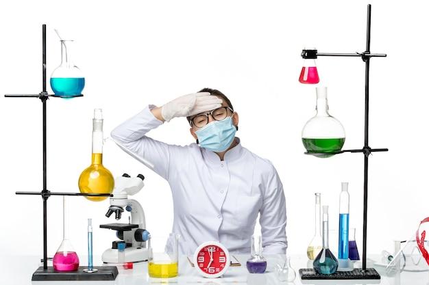 正面図白い背景の化学ウイルスラボcovid-スプラッシュで彼女の温度をチェックするマスクと医療スーツの女性化学者