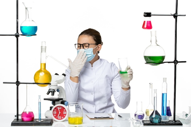 白い背景の上のマスク飲用溶液と医療スーツの正面図女性化学者スプラッシュラボウイルス化学covid