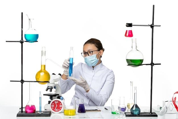Вид спереди женщина-химик в медицинском костюме с маской, держащей синий раствор на белом фоне, брызги вируса, химическая лаборатория covid