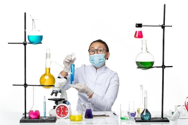 白い机の上の青いソリューションを保持しているマスクと医療スーツの正面図女性化学者スプラッシュウイルス化学covid