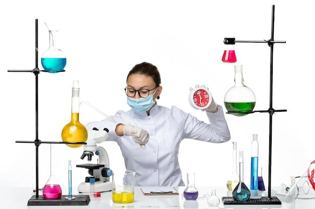 흰색 배경 바이러스 실험실 화학 covid- 시작에 그녀의 손목을보고 시계를 들고 마스크와 의료 소송에서 전면보기 여성 화학자