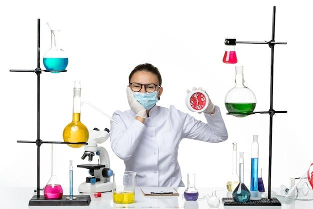 흰색 책상 바이러스 실험실 화학 covid 시작에 시계를 들고 마스크와 의료 소송에서 전면보기 여성 화학자