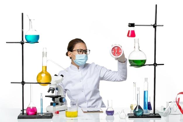 흰색 배경 바이러스 실험실 화학 covid 스플래시에 시계를 들고 마스크와 의료 소송에서 전면보기 여성 화학자