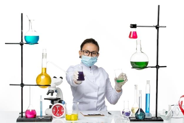 흰색 배경 스플래시 바이러스 화학 실험실 covid에 다른 솔루션을 들고 마스크와 의료 소송에서 전면보기 여성 화학자