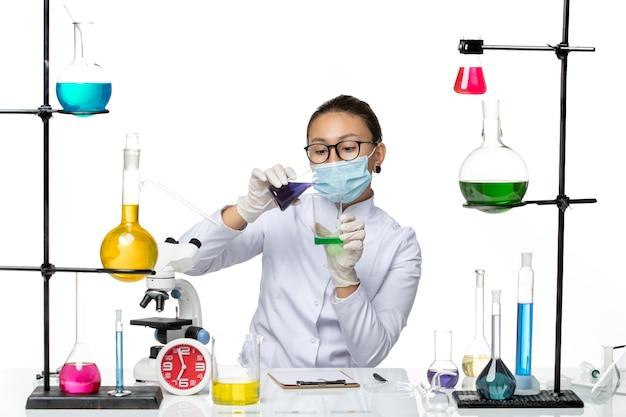 흰색 바닥 스플래시 바이러스 화학 실험실에 다른 솔루션을 들고 마스크와 의료 소송에서 전면보기 여성 화학자 covid