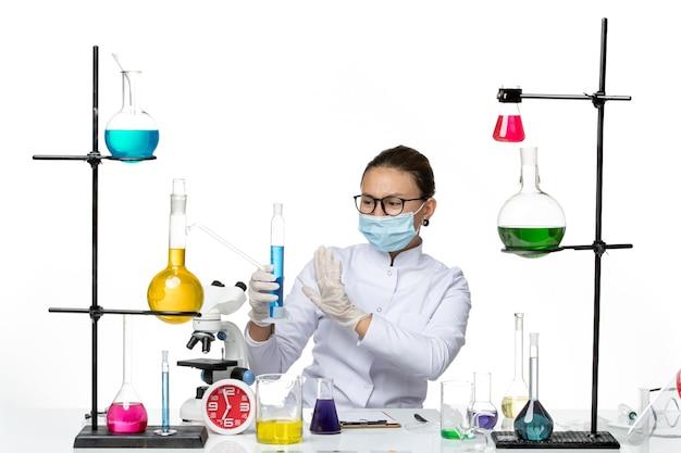 明るい白の背景に青い溶液とフラスコを保持しているマスクと医療スーツの正面図女性化学者スプラッシュウイルス化学実験室covid