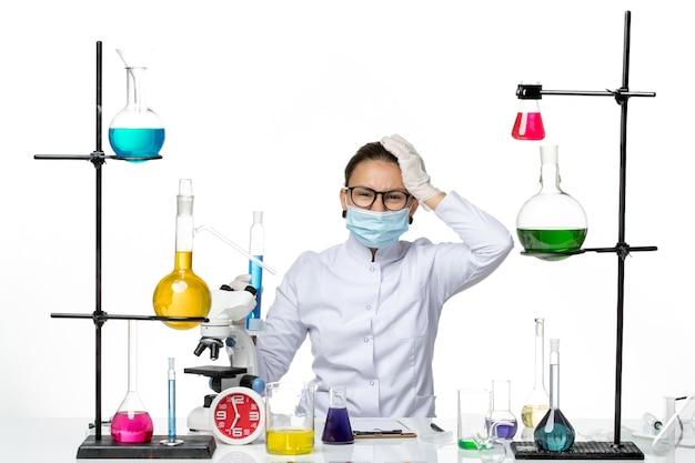 白い背景の上の青い溶液とフラスコを保持しているマスクと医療スーツの正面図女性化学者ウイルス化学実験室covidスプラッシュ