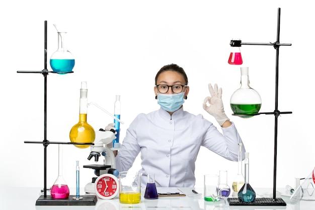 白い机の上の青い溶液とフラスコを保持しているマスクと医療スーツの正面図女性化学者スプラッシュウイルス化学実験室covid