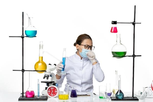 밝은 흰색 배경 스플래시 바이러스 화학 실험실 covid에 파란색 솔루션으로 플라스크를 들고 마스크와 의료 소송에서 전면보기 여성 화학자
