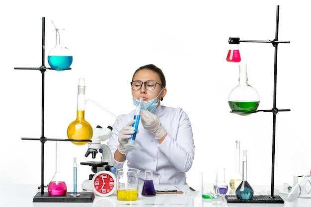 白い背景の上の青い溶液とフラスコを保持しているマスクと医療スーツの正面図女性化学者スプラッシュウイルス化学実験室covid