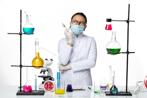 ライトホワイトの背景に注射を保持しているマスクと医療スーツの正面図女性化学者ウイルス化学実験室covidスプラッシュ