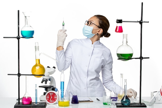 白い背景に注射を保持しているマスクと医療スーツの正面図女性化学者ウイルス化学実験室covidスプラッシュ