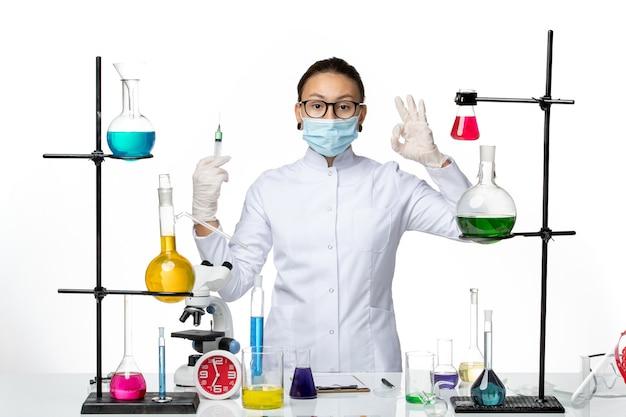白い机の上の注射を保持しているマスクと医療スーツの正面図女性化学者ウイルス化学実験室covidスプラッシュ