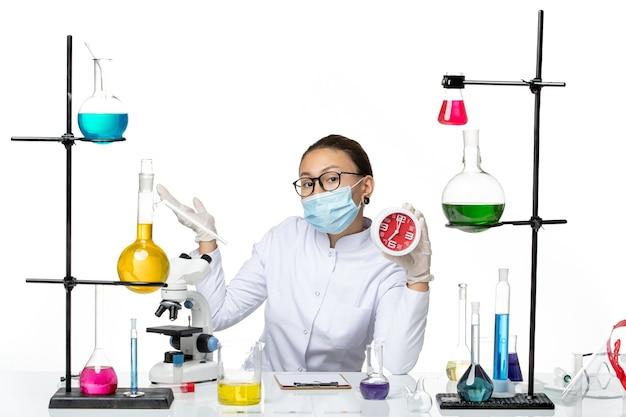 Вид спереди женщина-химик в медицинском костюме с маской, держащая красные часы на светлом белом фоне, вирусная лаборатория химии, covid- splash