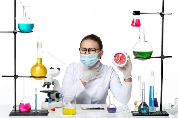 Вид спереди женщина-химик в медицинском костюме с маской, держащая красные часы на белом фоне, лаборатория химии вирусов covid- splash