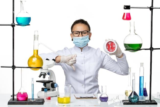 Вид спереди женщина-химик в медицинском костюме с маской, держащая красные часы на белом фоне, вирусная лаборатория, химия, covid- splash
