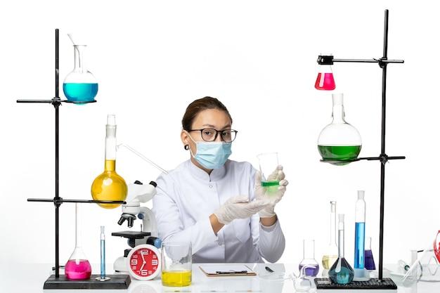 明るい白の背景に溶液を保持するマスクを備えた医療スーツの正面図の女性化学者スプラッシュラボウイルス化学covid-