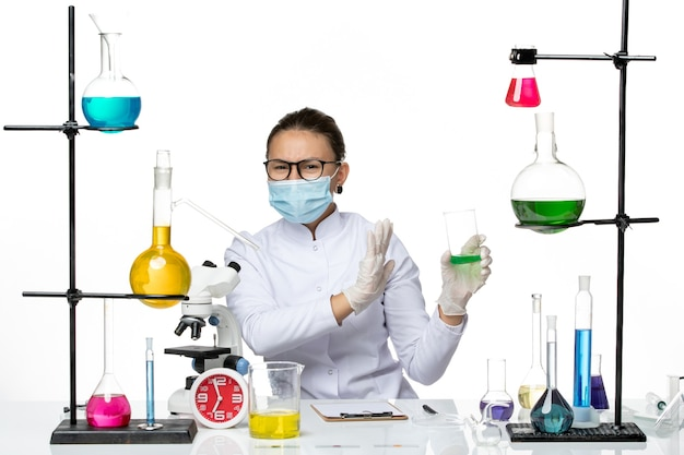 白い背景の上のマスク保持ソリューションと医療スーツの正面図女性化学者スプラッシュラボウイルス化学covid