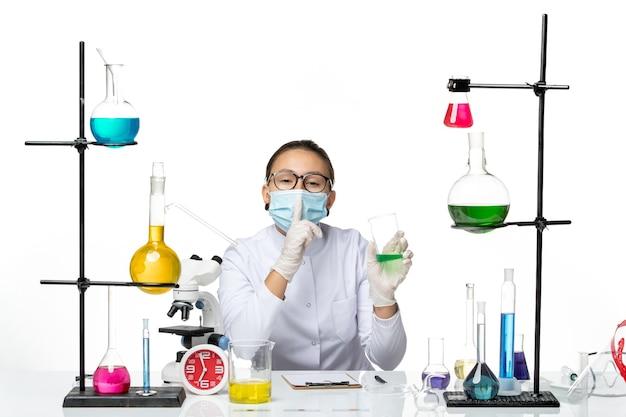 Вид спереди женщина-химик в медицинском костюме с маской, держащей раствор на белом столе, брызги лаборатории вирусной химии covid-