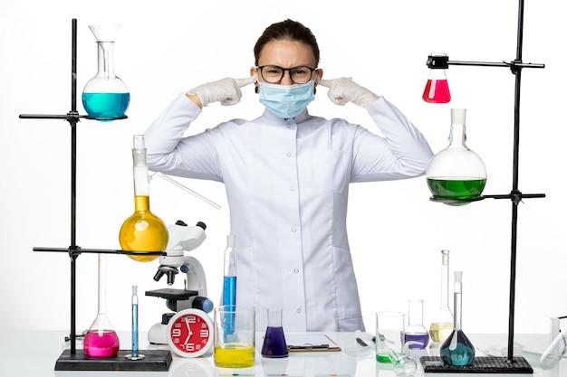 마스크가 흰색 배경 바이러스 화학 실험실 covid- 스플래시에 그녀의 귀를 닫는 의료 소송에서 전면보기 여성 화학자