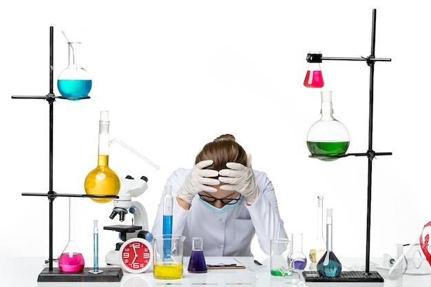 白い背景に疲れを感じているソリューションとテーブルの前に座っているマスクと医療スーツの正面図女性化学者ウイルス化学実験室covidスプラッシュ