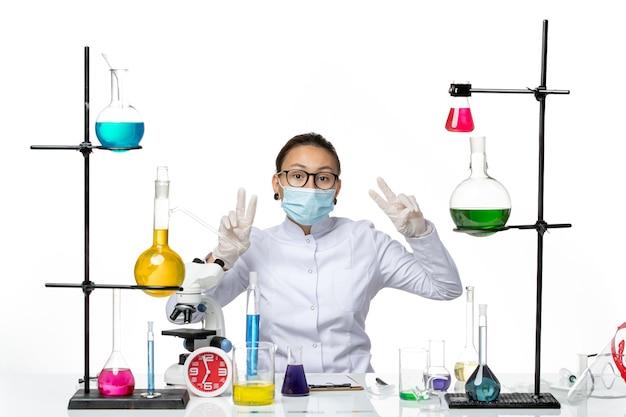 Вид спереди женщина-химик в медицинском костюме с маской, сидящая перед столом с растворами на белом столе, вирусная химическая лаборатория, всплеск covid