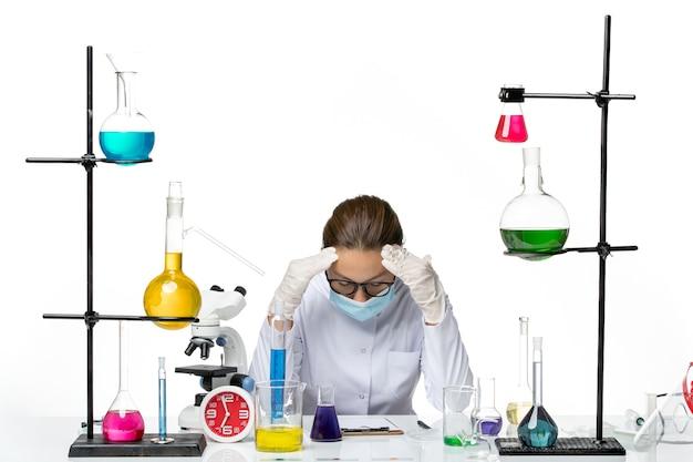 白い背景に疲れたソリューションでテーブルの前に座っているマスクと医療スーツの正面図女性化学者ウイルス化学実験室covidスプラッシュ