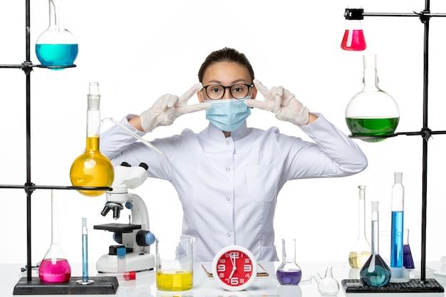 正面図白い背景の化学ウイルスcovid-スプラッシュにソリューションと一緒に座っているマスクと医療スーツの女性化学者