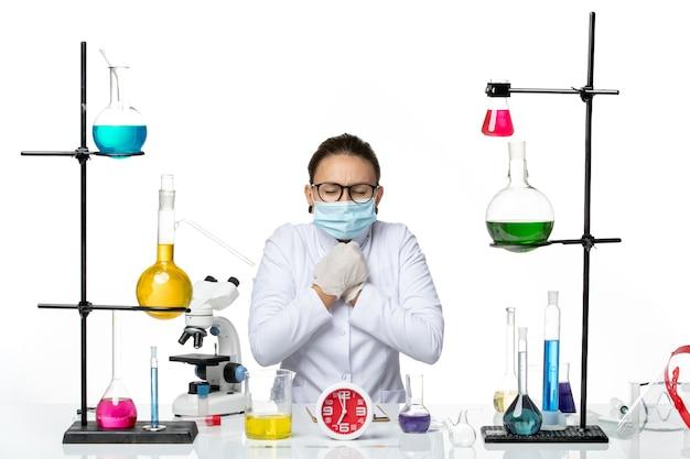 Вид спереди женщина-химик в медицинском костюме с маской, сидящая с дрожащими растворами на белом фоне, химическая лаборатория, вирус covid- splash
