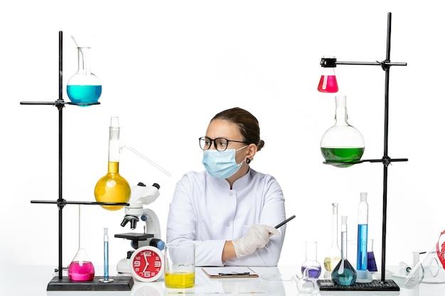 白い背景にメモを書くソリューションと一緒に座っているマスクと医療スーツの正面図女性化学者スプラッシュラボウイルス化学covid