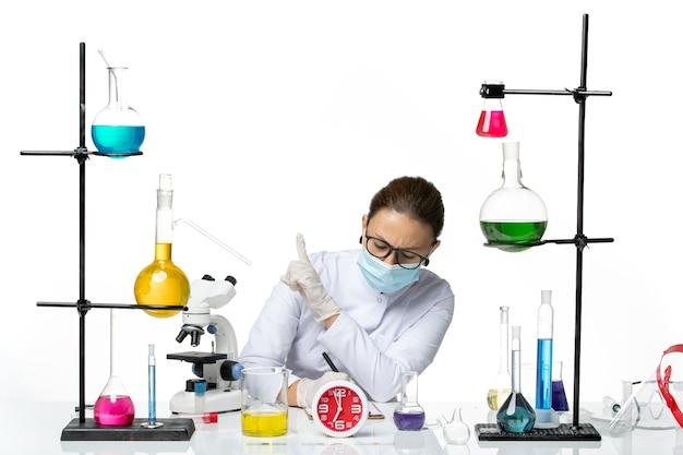 正面図白い背景の化学者ラボウイルスcovid-スプラッシュにメモを書くソリューションと一緒に座っているマスクと医療スーツの女性化学者
