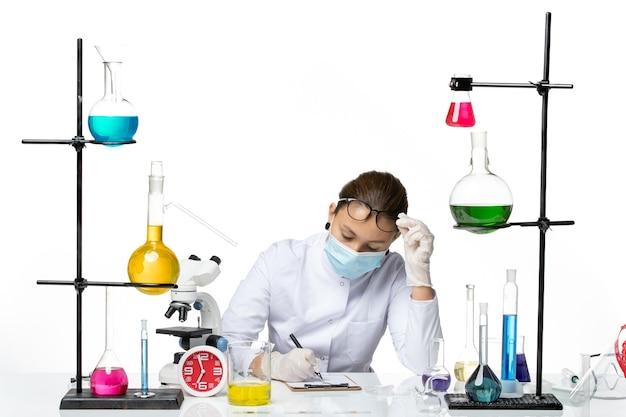 Вид спереди женщина-химик в медицинском костюме с маской сидит с растворами, пишет заметки на белом фоне, всплеск лаборатории вирусной химии covid