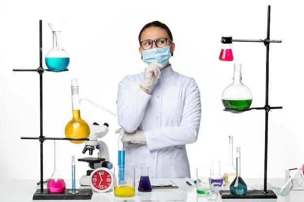 白い背景のウイルス化学実験室covid-スプラッシュでマスク思考と医療スーツの正面図女性化学者