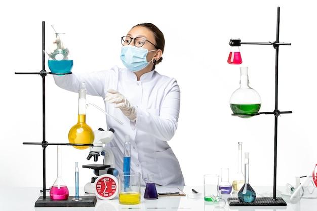 白い背景のウイルス化学実験室covidスプラッシュのソリューションで作業マスクと医療スーツの正面図女性化学者