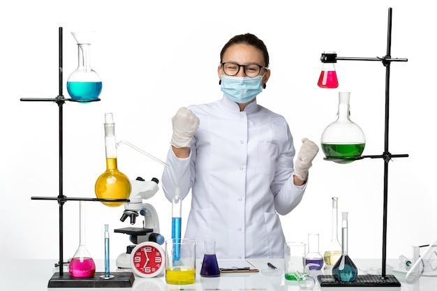 Вид спереди женщина-химик в медицинском костюме с маской, работающая с растворами на белом столе, вирусная химическая лаборатория, всплеск covid