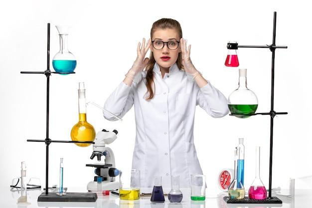 흰색 책상 화학 유행성 코로나 바이러스에 다른 솔루션으로 작업하는 의료 소송에서 전면보기 여성 화학자