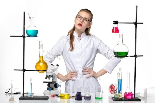白い背景の化学パンデミックコビッドウイルスにポーズをとってさまざまなソリューションで作業している医療スーツの正面図の女性化学者