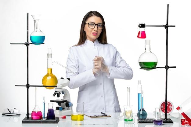 Вид спереди женщина-химик в медицинском костюме, работающая с растворами на белом столе, лабораторный вирус covid - наука о пандемии