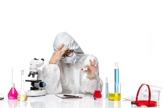 特別な防護服を着た女性化学者の正面図白い背景の化学コビパンデミック健康ウイルスのサンプルをチェック