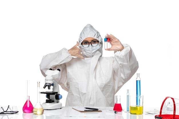 빈 플라스크를 들고 흰색 배경에 포즈를 취하는 특별 보호 복의 전면보기 여성 화학자 건강 바이러스 화학 covid