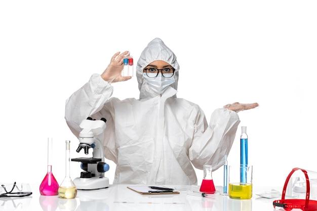 밝은 흰색 배경 바이러스 건강 화학 covid에 빈 플라스크를 들고 특수 보호 복에 전면보기 여성 화학자