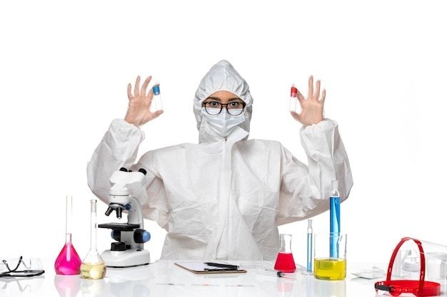 흰색 책상에 빈 플라스크를 들고 특수 보호 복에 전면보기 여성 화학자 바이러스 건강 화학 covid